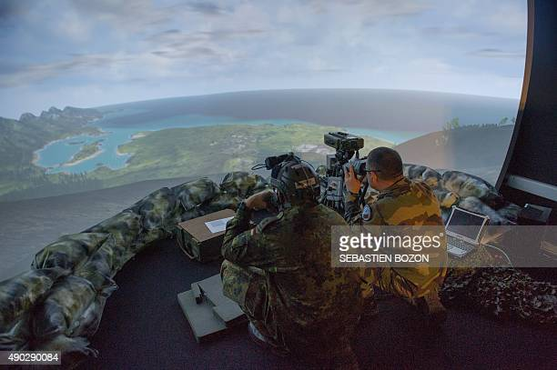 A photo taken on September 25 2015 shows a German and a French soldier using a simulator during a military exercise of groundguided strikes at the...