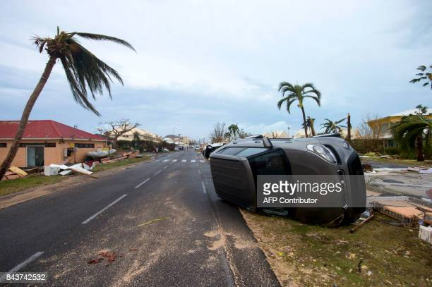Photo taken on September 6, 2017 shows a car turned onto its side in Marigot, near the Bay of Nettle, on the French Collectivity of Saint Martin,...