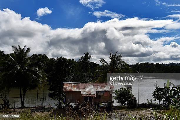 A photo taken on September 8 2014 shows a view of a house next to a river in the jungle of Papua New Guinea AFP PHOTO / ARIS MESSINIS