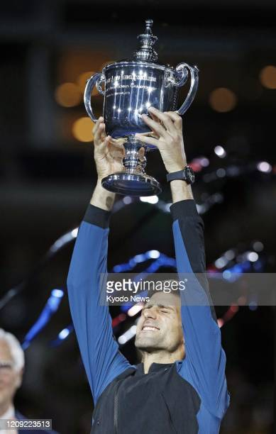 Photo taken Sept 9 shows Novak Djokovic of Serbia holding up his trophy after winning the US Open tennis tournament in New York
