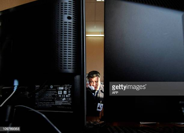 A photo taken through a gap between two computer monitors shows a police officer on duty speaking by phone in a police station in the ancient Russian...