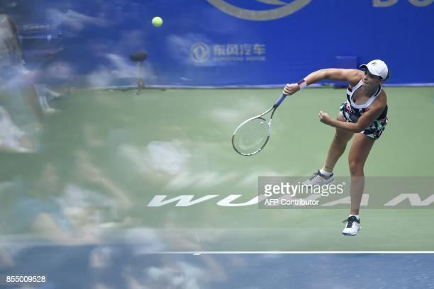 Photo taken through a glass pane shows Ashleigh Barty of Australia being refelected as she hits a return against Karolina Pliskova of Czech Repubic...