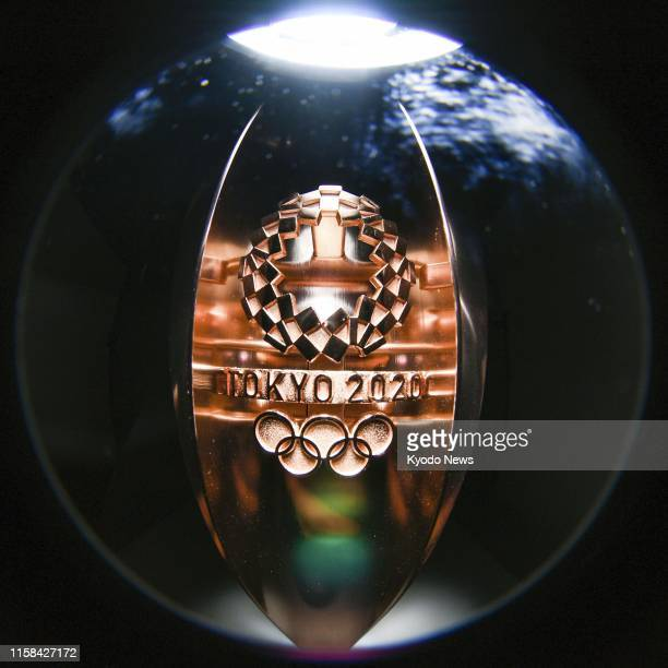 Photo taken with a fisheye lens on June 3 shows the Tokyo Olympic logo inscribed on the surface of a torch for the Olympic flame torch relay ==Kyodo