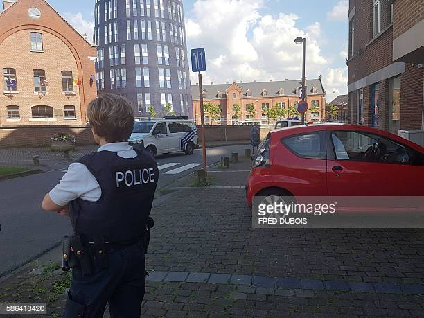 A photo taken with a mobile phone on August 6 shows a police officer standing guard close to a police building in the southern Belgian city of...