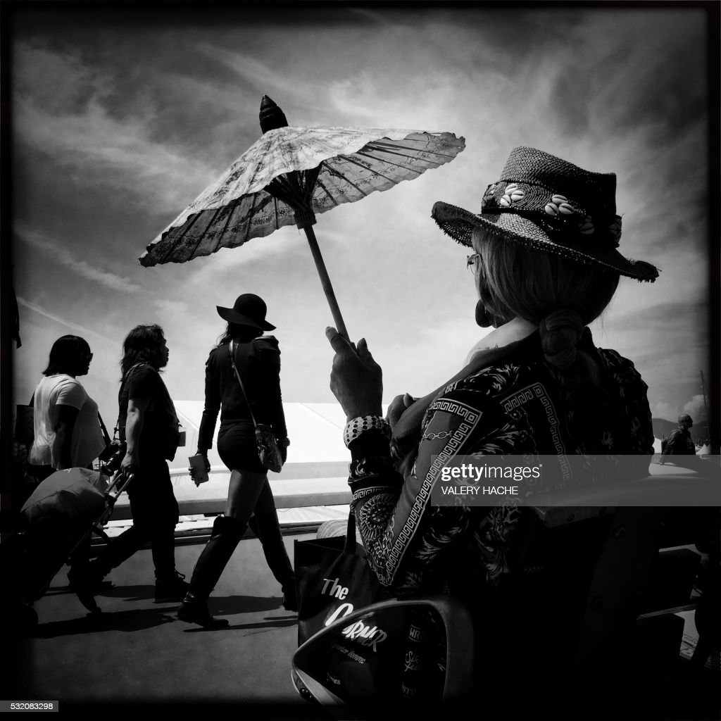 A photo taken with a mobile phone shows festival goers walking on the Croisette on May 18, 2016 during the 69th Cannes Film Festival in Cannes, southern France. / AFP PHOTO / Valery HACHE