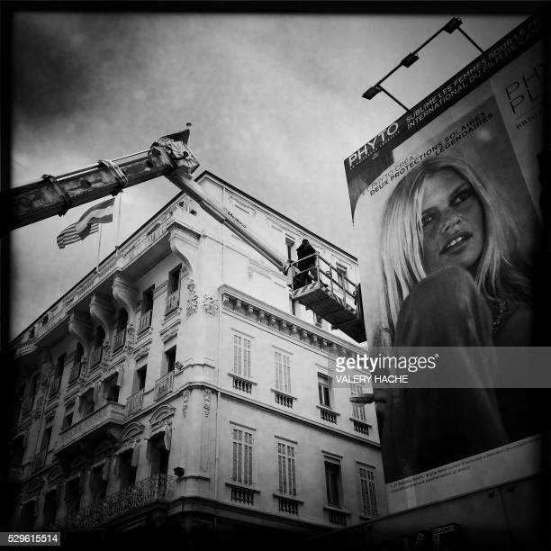 A photo taken with a mobile phone shows workers setting up a giant poster of the young French actress Brigitte Bardot before the 69th Cannes' film...