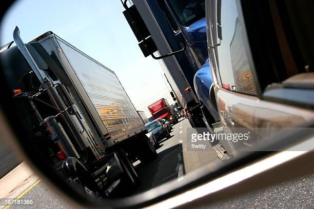 Photo view in rearview mirror trucks in traffic on roadway