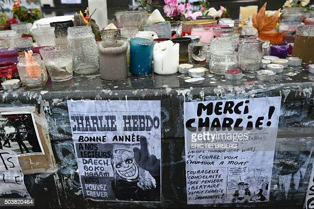 TOPSHOT A photocopy of Charlie Hebdo reading 'Happy New Year to our readers IS Boko Hara go to hell' is seen on a makeshift memorial on the place de...