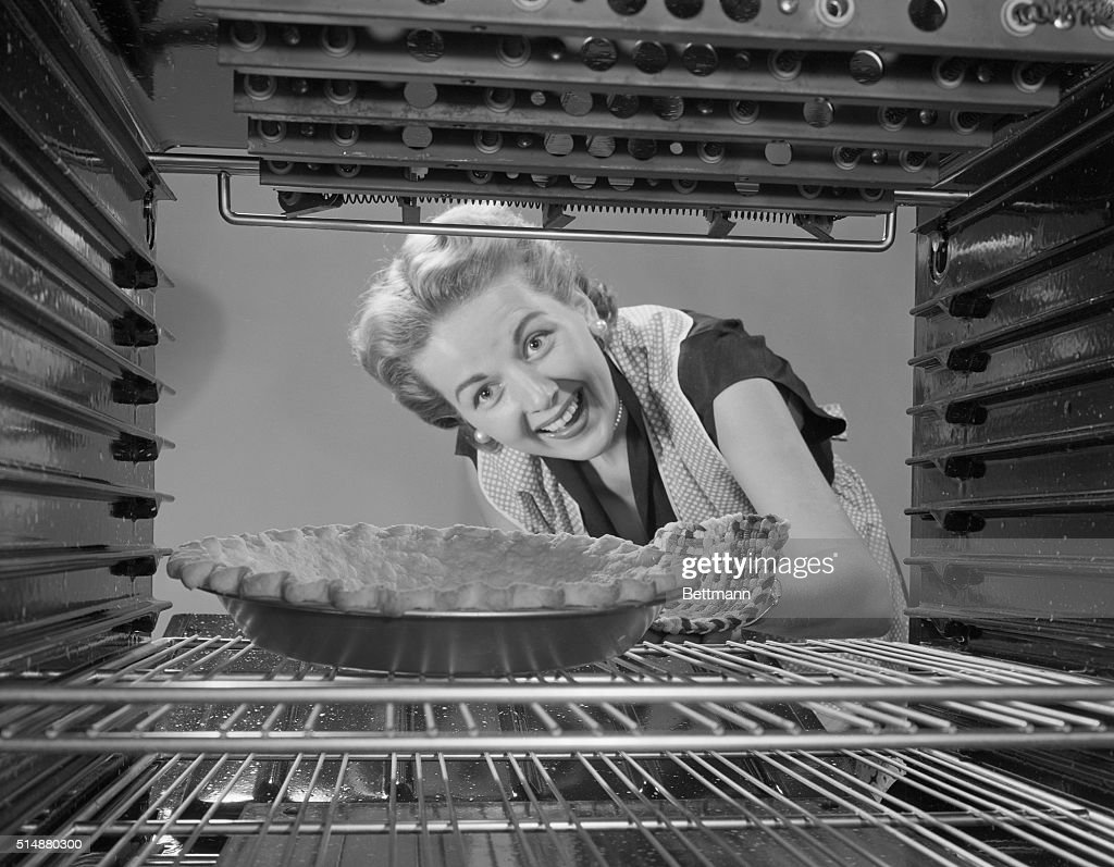 Woman Looking at Pie in Oven : News Photo