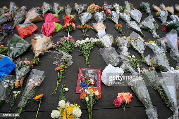 A photograph and floral tributes sit beside a statue of the former South African President Nelson Mandela on Nelson Mandela Square following the...