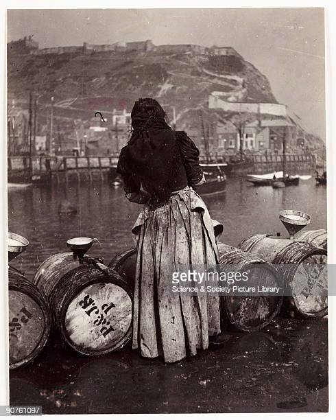 Photograph by Frank Meadow Sutcliffe The woman is probably pouring salt water into the funnels to keep the contents of the barrels fresh The cliffs...