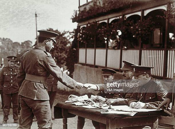 UNITED KINGDOM JULY 19 Photograph by Horace W Nicholls A group of officers and NCOs sit at a table possibly giving out chits or pay to the men