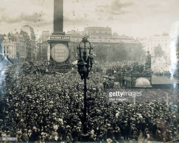 Photograph by Horace W Nicholls of crowds celebrating the end of the First World War Hoardings round Nelson's Column read 'Victory loan our duty...