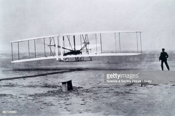 Photograph by John Daniels Orville Wright at the controls of the 'Flyer' at Kitty Hawk North Carolina USA watched by his brother Wilbur on foot One...