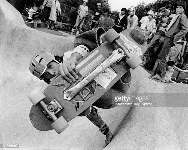 Photograph by Ken Lennox of a teenager performing a stunt on a skateboard watched by spectators A trophy is visible at top left