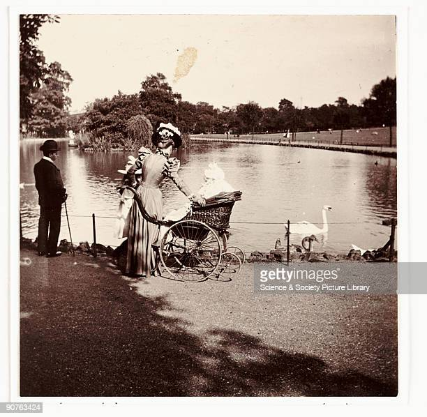 A photograph by Paul Martin around 1900 of a London lakeside scene An elegantly dressed woman and girl stand next to a person in a wheelchair by the...