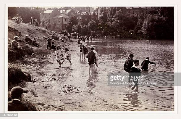 A photograph by Paul Martin of children playing in a river taken about 1900 A hot summer's day A large group of children play along the river's edge...