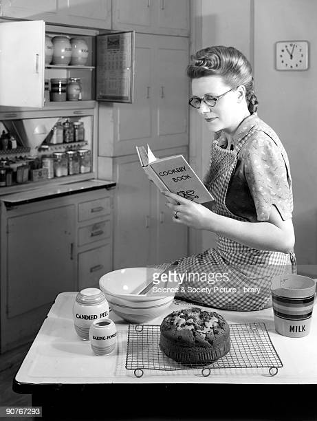 A photograph by Photographic Advertising Limited A freshly baked fruit cake sits on the table in front of her This photograph was taken in...
