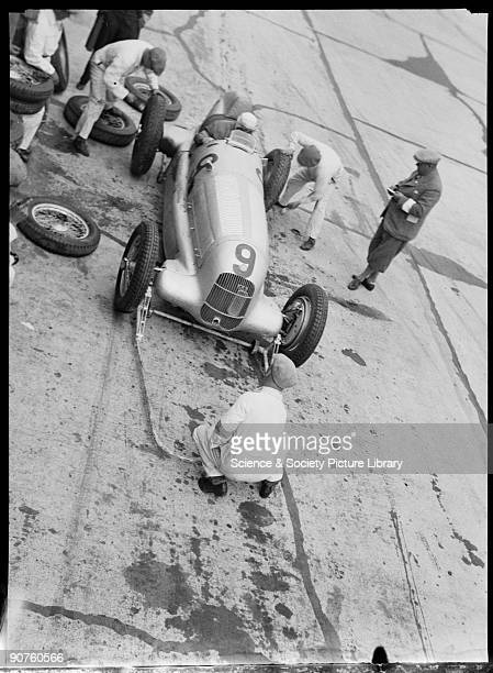 Photograph by Zoltan Glass Mechanics preparing Fagioli�s MercedesBenz W25 GP racing car Alfred Neubauer manager of the Mercedes Grand Prix team...
