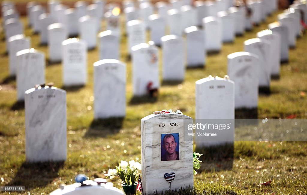 A photograph covers the back of the headstone of Lance Corporal Daniel R. Bennett, of Clifton, Virginia in Section 60 at Arlington National Cemetery March 15, 2013 in Arlington, Virginia. Section 60 is the section of the cemetery where American military members killed in Iraq and Afghanistan are currently laid to rest, though soldiers and Marines from World War II through Afghanistan are also buried in the section. March 20th marks the ten-year anniversary of the beginning of the war in Iraq. Bennett died January 11, 2009, as a result of a non-hostile incident in Helmand province, Afghanistan.