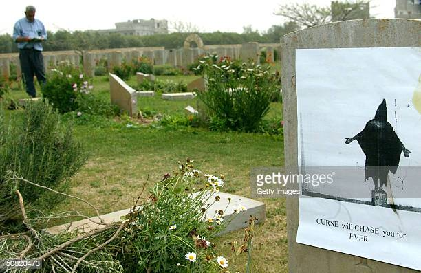 A photograph depicting the abuse of an Iraqi prisoner in Abu Ghraib prison is seen attached to a gravestone at the Commonwealth military cemetery May...