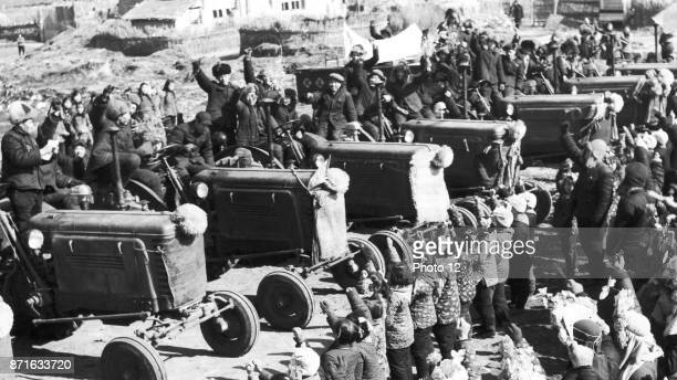 Photograph from the 'Great Leap Forward' Campaign Chinese villagers from Chung Haing Hsiang in the Pai Chuan Province welcome the arrival of tractors...