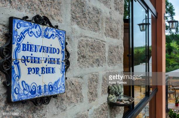 photograph in high resolution horizontally, plaque written welcome who comes for the good in the Spanish language, blue tile on external wall in apparent brick in clear afternoon in são paulo in brazil