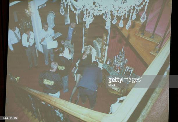 A photograph is projected as evidence detailing the view from the stairs in the foyer of Phil Spector's house where investigators gathered around the...