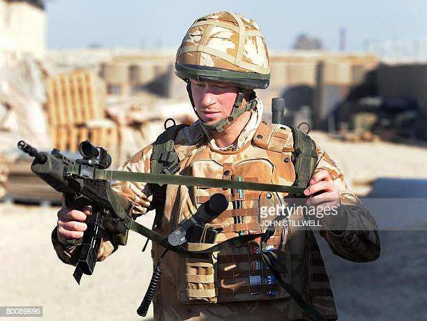 A photograph made available February 28 shows Britain's Prince Harry as he holds his SA80 rifle as he prepares to patrol through the deserted town of...