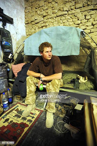 A photograph made available February 28 shows Britain's Prince Harry as he sits on his camp bed in his accommodation at FOB Delhi in Helmand province...