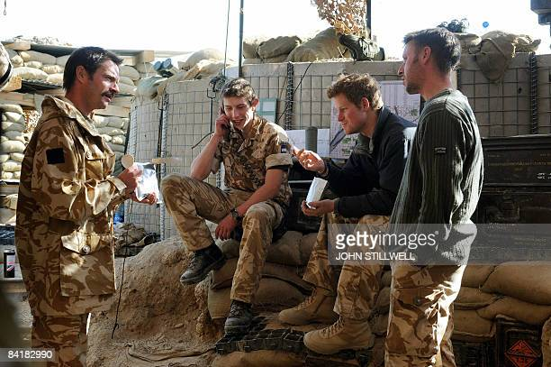 A photograph made available February 28 shows Britain's Prince Harry as he sits with other soldiers in an area of the observation post on JTAC Hill...