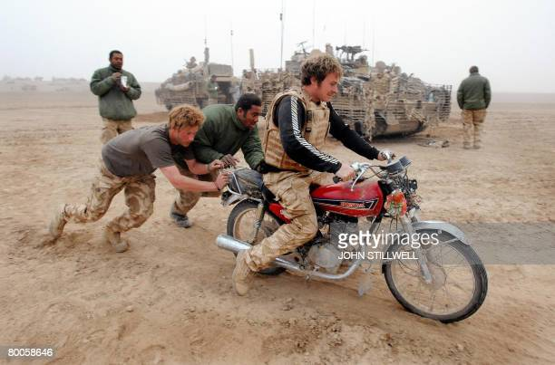 A photograph made available on February 28 shows Britain's Prince Harry pushing start an abandoned motorcycle ridden by Lance Cpl Steve 'Geri'...