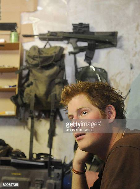A photograph made available on February 28 shows Britain's Prince Harry as he sits on his camp bed in his accommodation at FOB Delhi in Helmand...