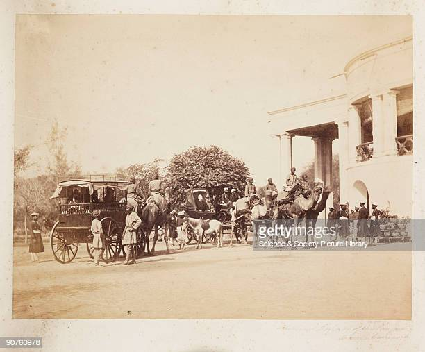 A photograph of a British colonial administrator and his camel carriages in the Punjab India taken by Samuel Bourne The lieutenant dressed in his...