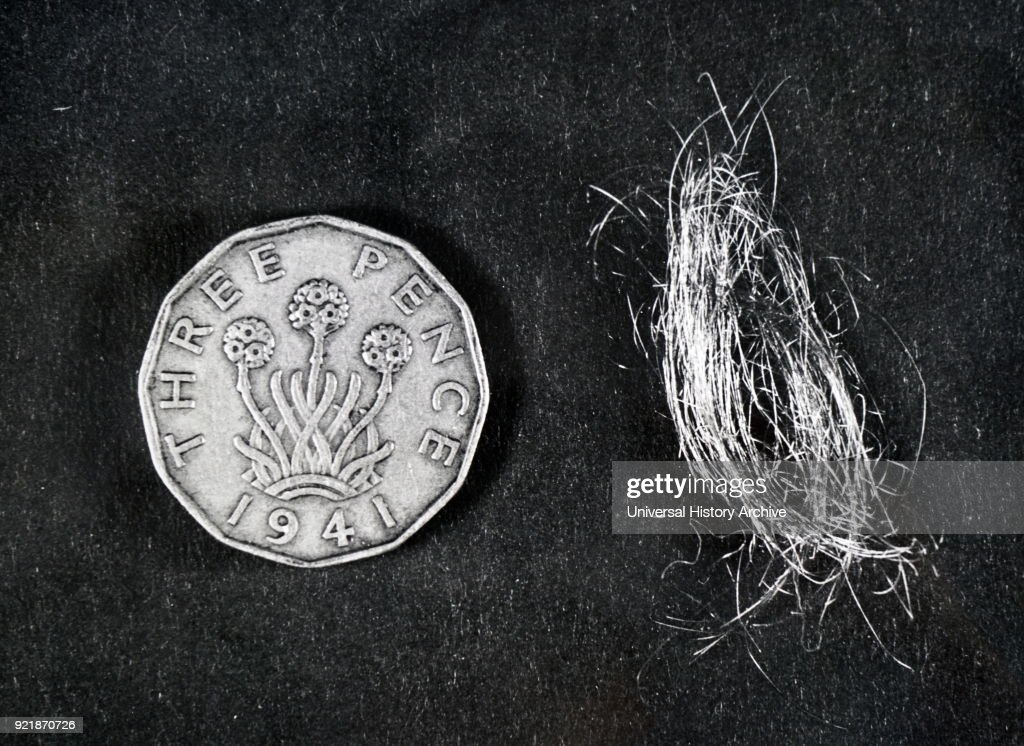 Photograph of a bundle of 500 space needles compared in size with a threepenny piece. Dated 20th century.