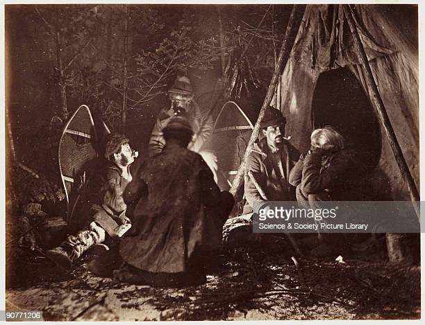 A photograph of a camp scene with a group of hunters gathered around a campfire next to their tent taken by William McFarlane Notman in 1860 This...