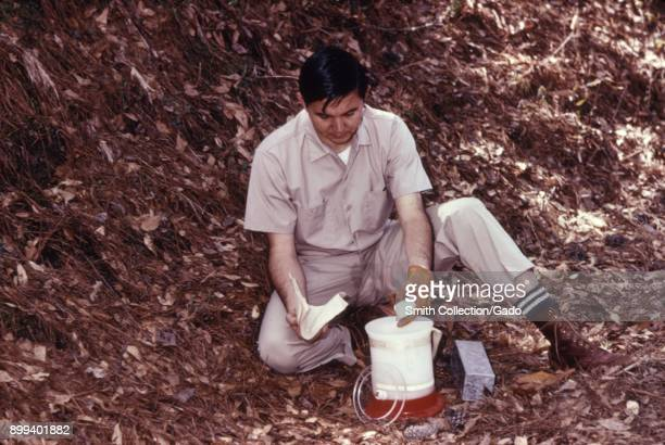 Photograph of a CDC scientist wearing khaki field clothes preparing dry ice outdoors in order to anesthetize animals caught as part of a field study...