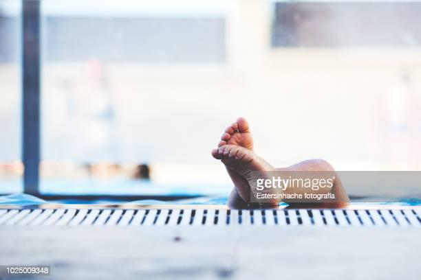 photograph of a child's feet coming out of a pool - piscina pubblica all'aperto foto e immagini stock