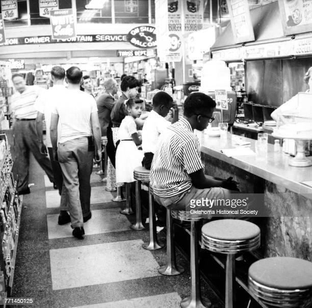 Photograph of a Civil Rights sit-in led by Clara Luper to desegregate the lunch counter at Katz Drug Store at Main and Robinson in downtown Oklahoma...