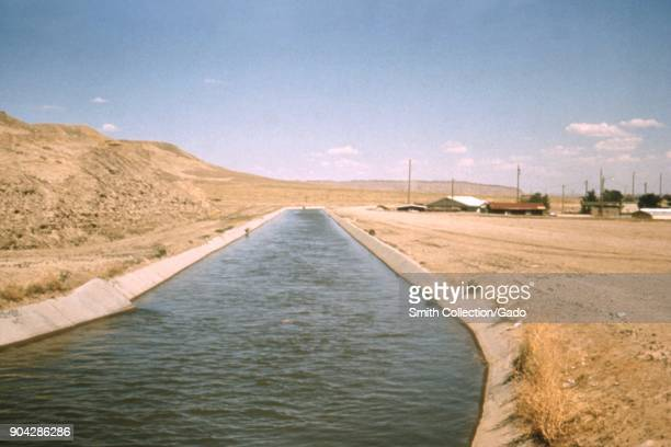 Photograph of a concrete lined irrigation distribution canal going through arid landscape in New Mexico with some houses visible in the distance a...