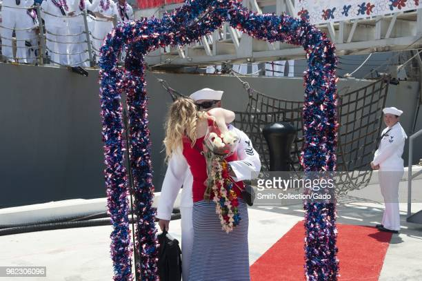 Photograph of a couple embracing in front of the guidedmissile destroyer USS Halsey recently returned from a sevenmonth deployment May 14 2018