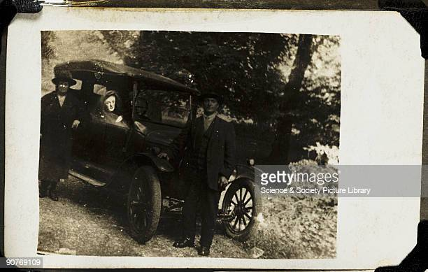A photograph of a couple leaning against a car taken by William Hope Two of Hope's friends are seen with a figure the couple's deceased son at the...