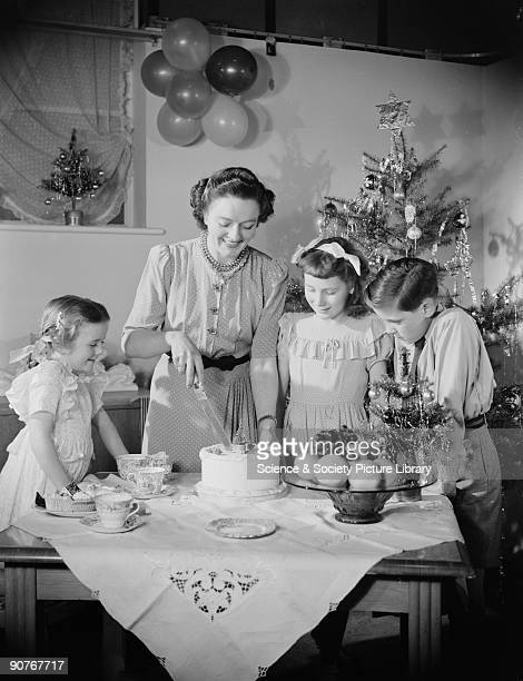 A photograph of a family gathered around the table at Christmas as the mother cuts a slice of cake taken by Photographic Advertising Limited in 1955...