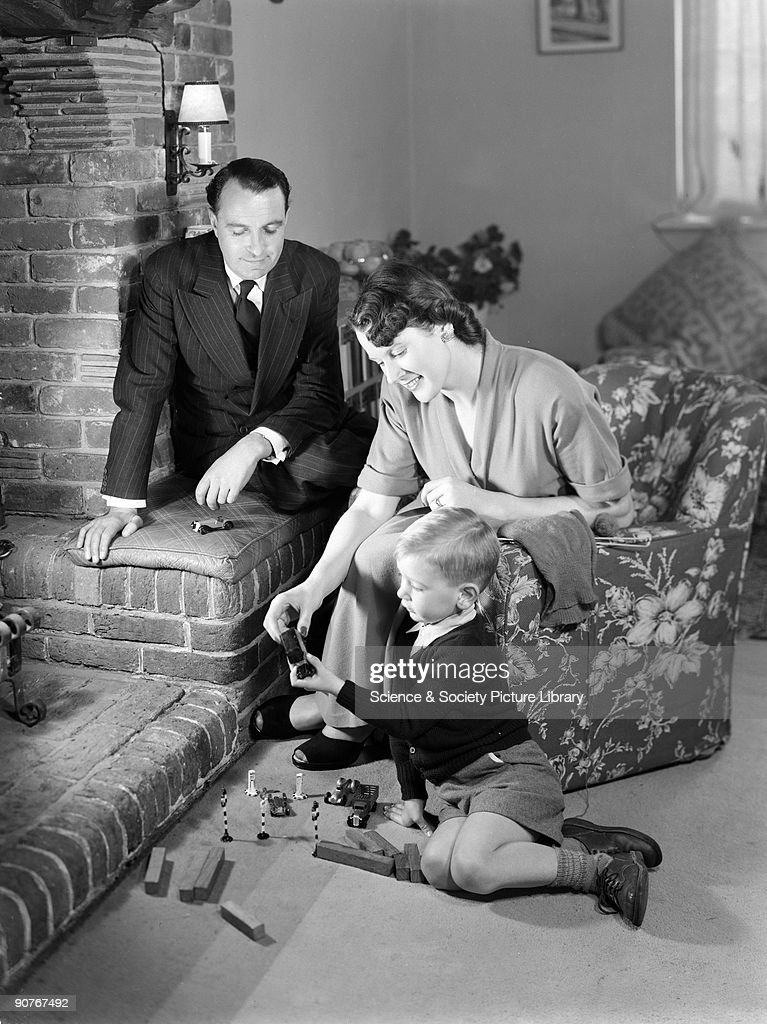 Little boy playing at the feet of his parents, 1952. : News Photo