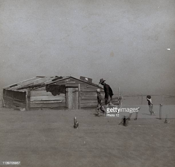 Photograph of a farmer and son walking in the face of a dust storm in Cimarron County Oklahoma Photograph taken by Arthur Rothstein