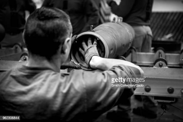 Photograph of a French sailor assisting in a simulated bomb build aboard the aircraft carrier USS George HW Bush as part of a project to strengthen...
