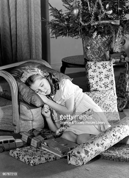 A photograph of a girl asleep beneath the Christmas tree surrounded by presents taken by Photographic Advertising Limited in about 1950 Christmas is...