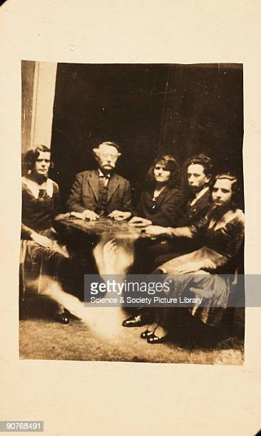 A photograph of a group gathered at a seance taken by William Hope The information accompanying the spirit album states that the table is levitating...