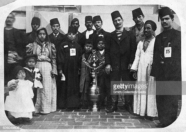 A photograph of a group of immigrants on Ellis Island most of the men and some of the boys are wearing fezzes there are several young children in...