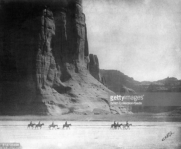 Photograph of a group of Native American men riding horses in the desert in front of the Canyon de Chelly titled 'Canyon de Chelly ' by Edward S...